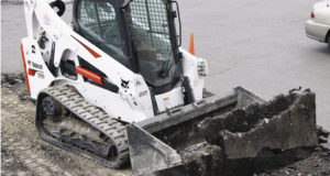 A Bobcat T590 compact track loader uses a bucket to move asphalt.