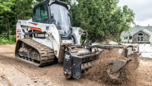 A T550 compact track loader uses a soil conditioner to prepare ground on a residential construction site.