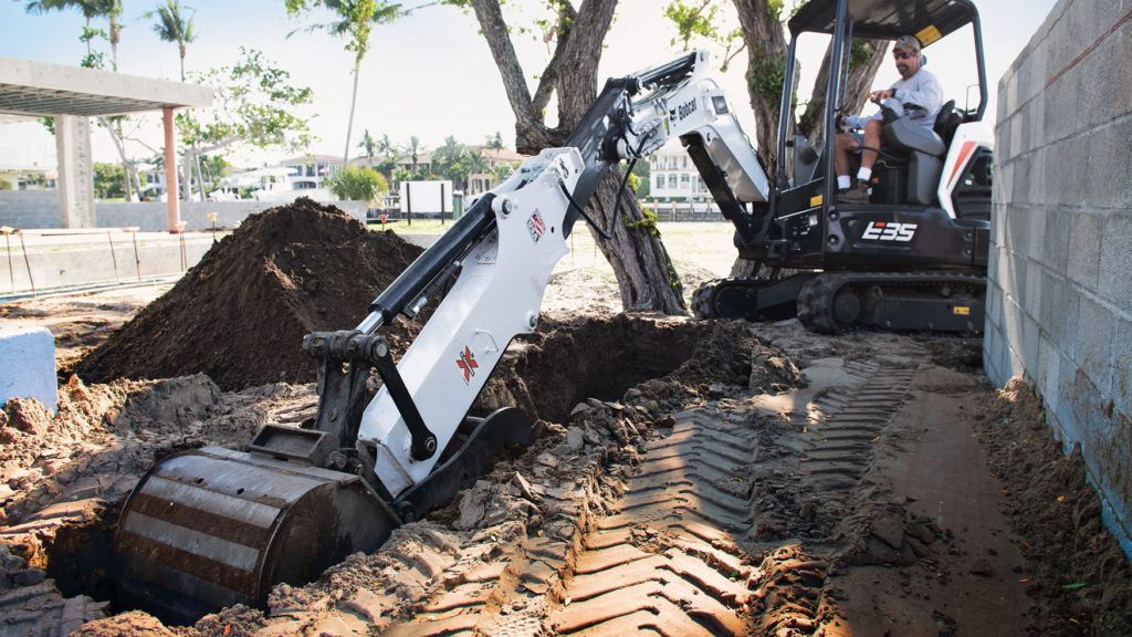 Bobcat mini excavator with an extendable arm digging a trench