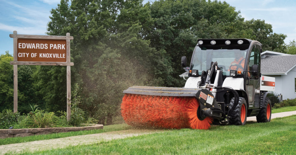 Toolcat 5600 clears sidewalk with Bobcat angle broom attachment.