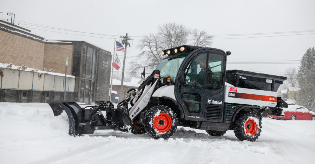 Toolcat 5600 clears snow in parking lot.