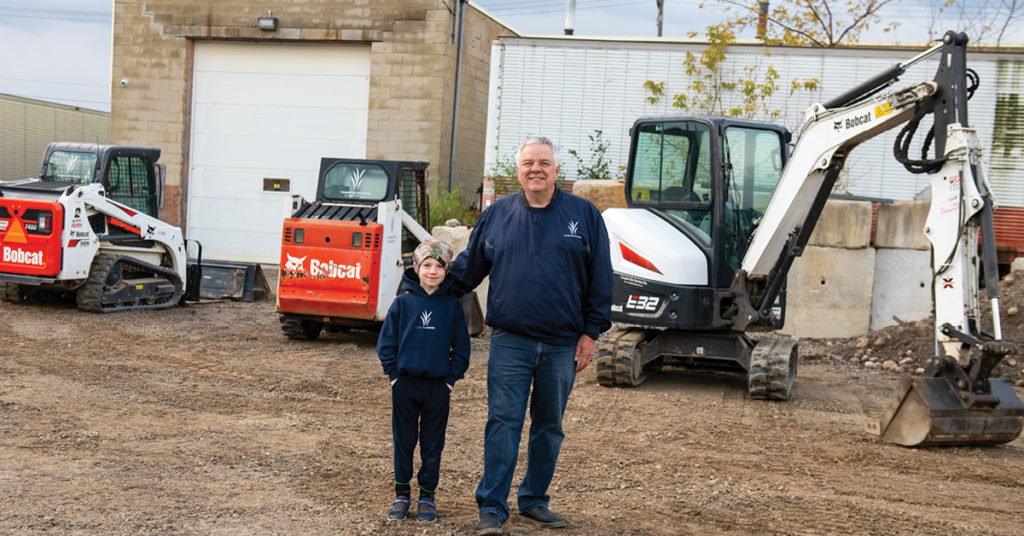 Rick Alischer and his grandson stand in front of the company's Bobcat fleet.