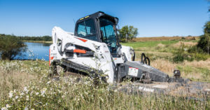 A T770 compact track loader paired with a rotary cutter mows an overgrown field.