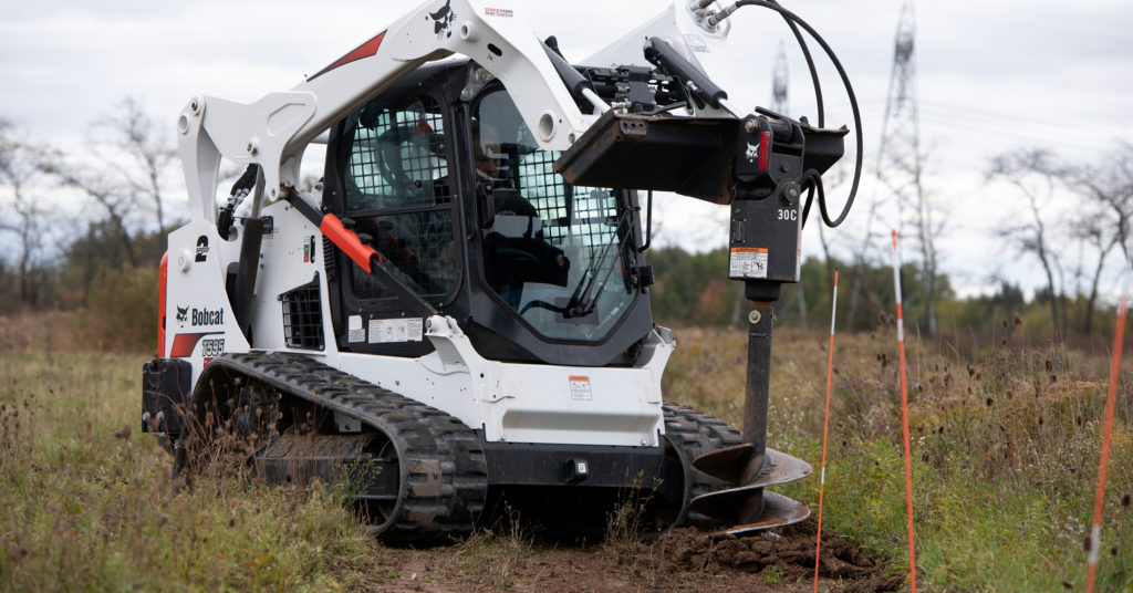 An operator in a Bobcat T595 with an auger drills a post hole