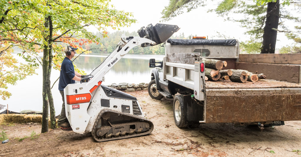 Operator uses an MT85 to load logs into a truck bed at a lakeside jobsite.