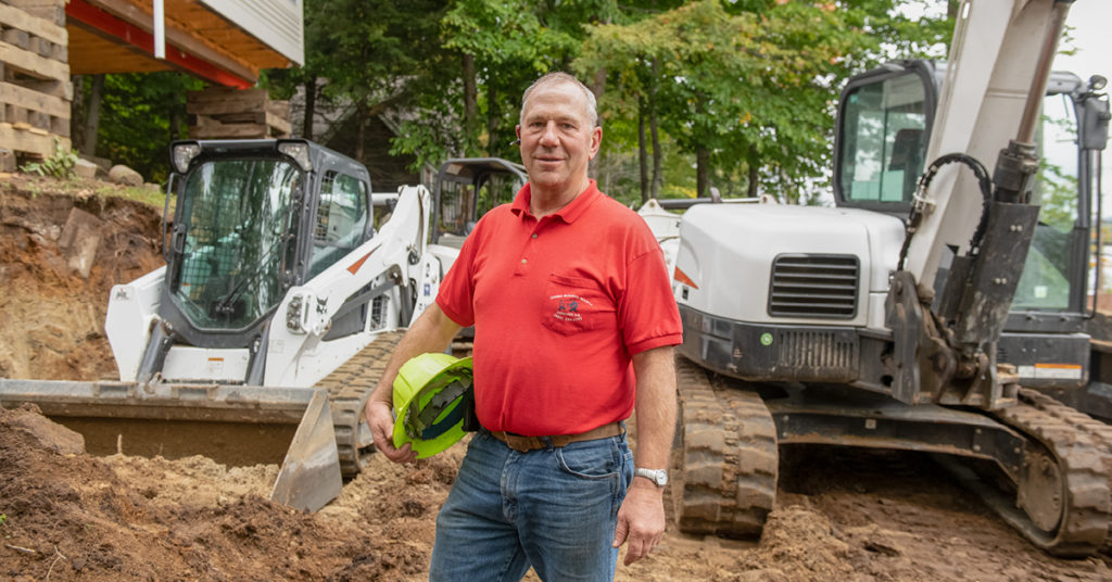Rick Geddes stands in front of his Bobcat compact track loader and mini excavator on a construction jobsite.