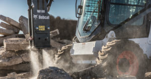 Bobcat skid-steer loader breaking concrete with a breaker attachment