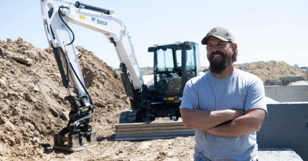 Dave Kling stands in front of Bobcat excavator.