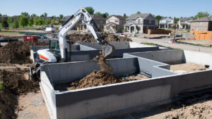 Bobcat excavator dumps dirt with bucket attachment.