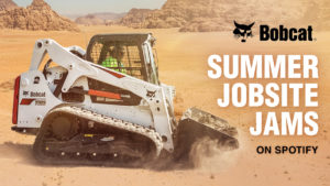 : A Bobcat T650 compact track loader carries dirt with its bucket attachment in the desert.