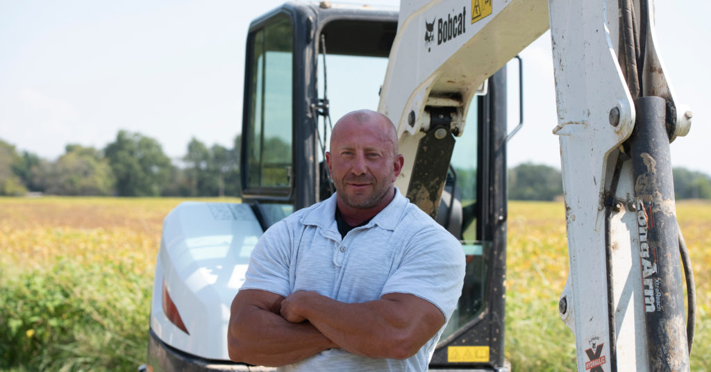 Contractor Jason Green stands with his Bobcat E35 compact excavator.