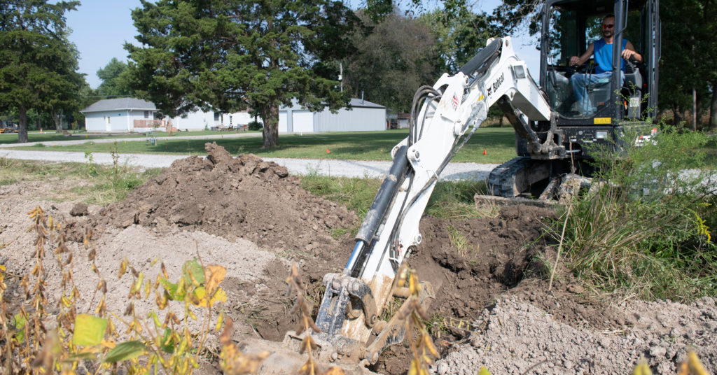 Bobcat mini excavator digs from the roadway.