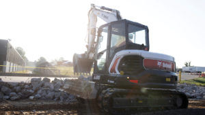 Bobcat E85 mini excavator moves broken concrete with a bucket