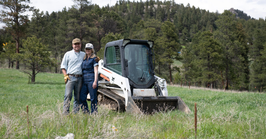 Heidi and Erik Bradberry stand in their pasture with a Bobcat compact track loader.