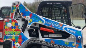 Bobcat compact track loader custom-wrapped to support autism awareness.