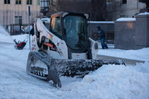 Bobcat Compact Track Loader navigates tight spaces to clear snow.