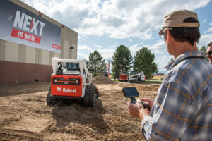 Man using the Bobcat MaxControl System to operate a Bobcat compact track loader.