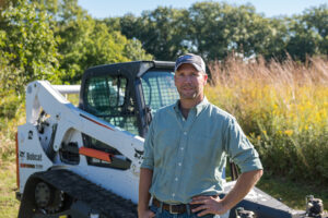 Chase Burns, Owner of Dogwood Land Management, Stands With His Bobcat Compact Track Loader