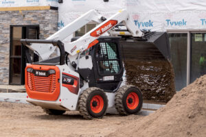 Construction Worker Dumps Dirt at a Jobsite Using the New Bobcat R-Series Compact Loader