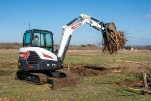 Bobcat Mini Excavator Moving Large Roots and Dirt