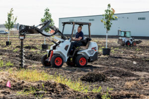 Landscaper Using A Bobcat Articulated Loader And Auger Attachment To Plant Trees