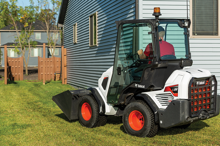Landscaper Driving Compact Loader Next To A House