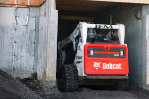 Bobcat Track Loader Grades Foundation For Home Through Narrow Entryway