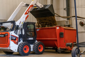 Operator Dumps Soil Using Bucket Attachment On Bobcat R-Series Skid-Steer Loader