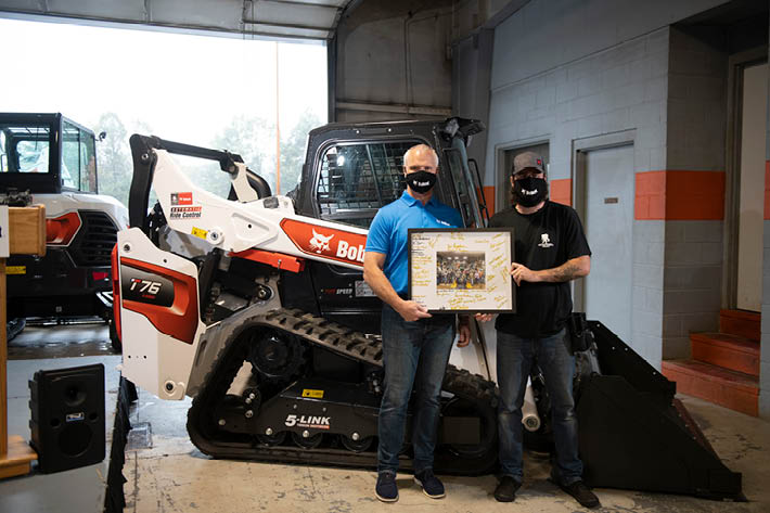 Mike Ballweber And Andrew Long Pose With Plaque In Front Of New Bobcat Compact Track Loader