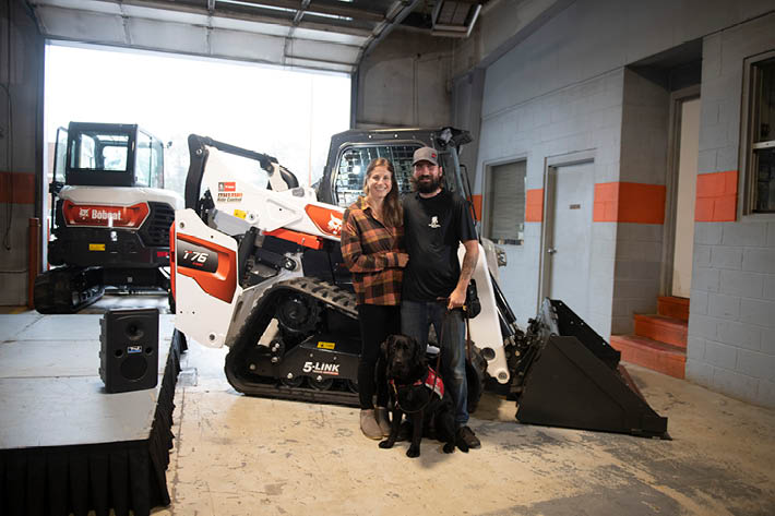 Andrew Long Poses With Fiance Caroline And Service Dog In Front Of New Bobcat Compact Track Loader