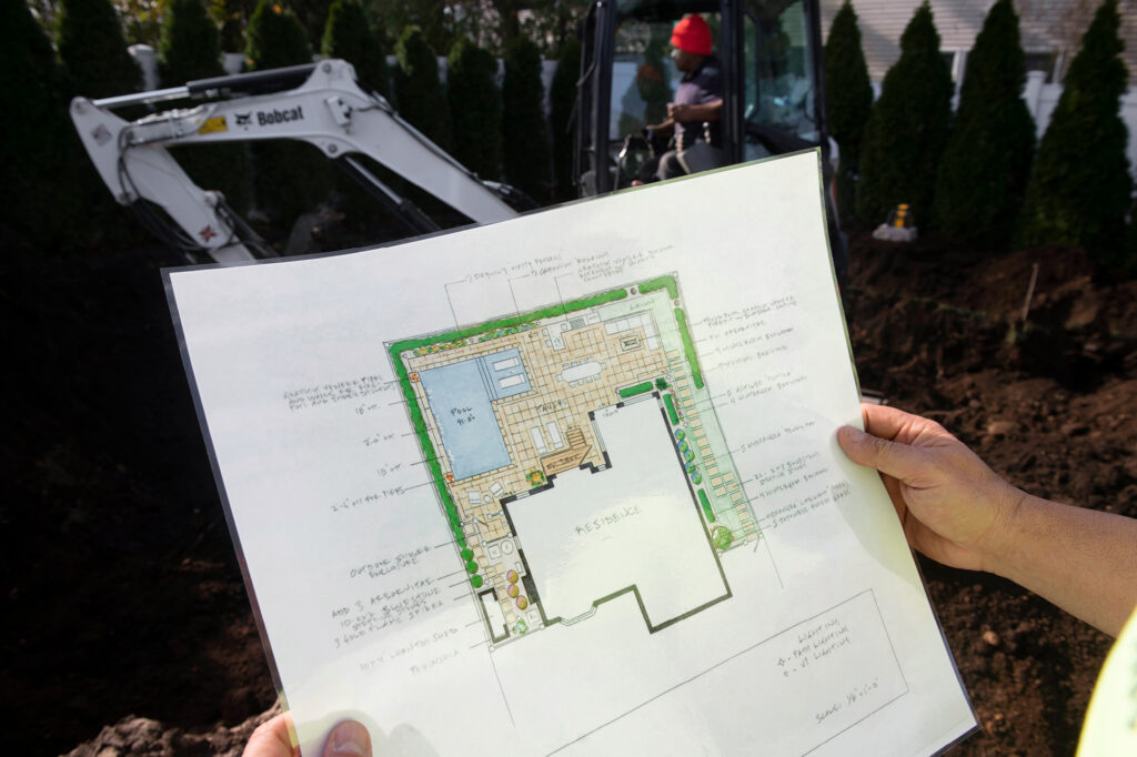 Blueprint For Backyard Pool With Bobcat Excavator Operating In The Background