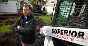 Landscaping Professional Stands In Front Of Bobcat Compact Track Loader And Mini Excavator